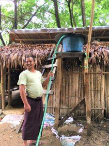 鶏小屋に給水する男性